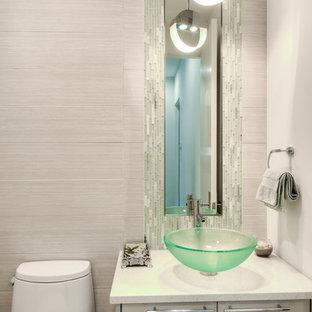 Immagine di un bagno di servizio minimalista di medie dimensioni con ante lisce, ante grigie, pareti grigie, lavabo a bacinella e top in superficie solida