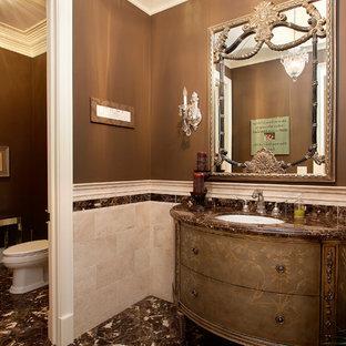 Idée de décoration pour un grand WC et toilettes tradition avec un placard en trompe-l'oeil, des portes de placard marrons, un WC séparé, un carrelage beige, du carrelage en travertin, un mur marron, un sol en marbre, un lavabo encastré, un plan de toilette en marbre et un sol marron.