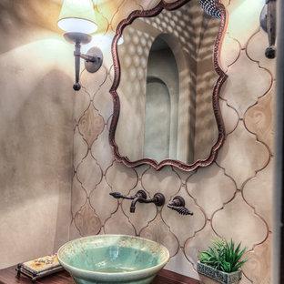Kleine Mediterrane Gästetoilette mit flächenbündigen Schrankfronten, dunklen Holzschränken, Wandtoilette mit Spülkasten, beiger Wandfarbe, Terrakottaboden, Aufsatzwaschbecken, Waschtisch aus Holz, rotem Boden und brauner Waschtischplatte in Houston