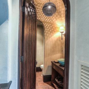 Свежая идея для дизайна: маленький туалет в средиземноморском стиле с плоскими фасадами, темными деревянными фасадами, раздельным унитазом, бежевыми стенами, полом из терракотовой плитки, настольной раковиной, столешницей из дерева и красным полом - отличное фото интерьера