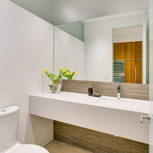 Inspiration for a medium sized modern cloakroom in Tampa with solid surface worktops, a two-piece toilet, concrete flooring, multi-coloured tiles, glass tiles, white walls and a submerged sink.