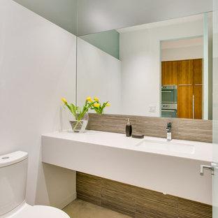 Свежая идея для дизайна: туалет среднего размера в стиле модернизм с столешницей из искусственного камня, раздельным унитазом, бетонным полом, разноцветной плиткой, стеклянной плиткой, белыми стенами и врезной раковиной - отличное фото интерьера