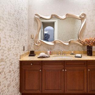 Mittelgroße Mediterrane Gästetoilette mit profilierten Schrankfronten, hellbraunen Holzschränken, Toilette mit Aufsatzspülkasten, beiger Wandfarbe, Unterbauwaschbecken, Marmor-Waschbecken/Waschtisch und gelber Waschtischplatte in Miami