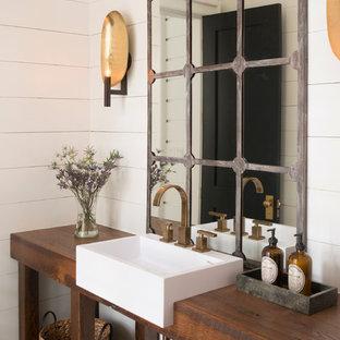 Modelo de aseo de estilo de casa de campo, de tamaño medio, con armarios tipo mueble, paredes blancas, encimera de madera, puertas de armario de madera en tonos medios, lavabo encastrado y encimeras marrones