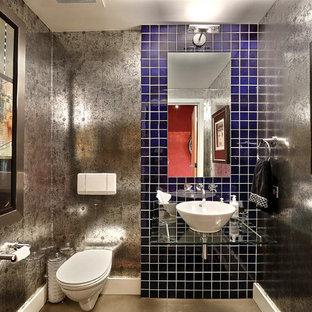 Réalisation d'un WC et toilettes urbain avec une vasque, un plan de toilette en verre, un WC suspendu et un carrelage bleu.