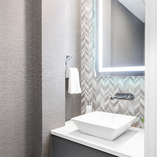 This is an example of a small contemporary cloakroom in Vancouver with flat-panel cabinets, grey cabinets, multi-coloured tiles, mosaic tiles, grey walls, medium hardwood flooring, a vessel sink, brown floors, white worktops and engineered stone worktops.