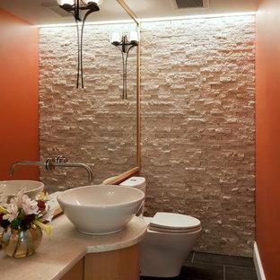 Inspiration pour un petit WC et toilettes traditionnel avec une vasque, un placard à porte plane, des portes de placard en bois clair, un plan de toilette en granite, un WC séparé, un mur orange, un sol en carrelage de céramique, un carrelage blanc et un carrelage de pierre.