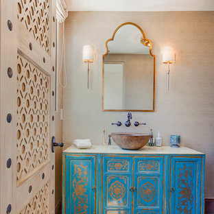 Inspiration for a mid-sized mediterranean medium tone wood floor powder room remodel in Los Angeles with a vessel sink, furniture-like cabinets, blue cabinets and beige walls