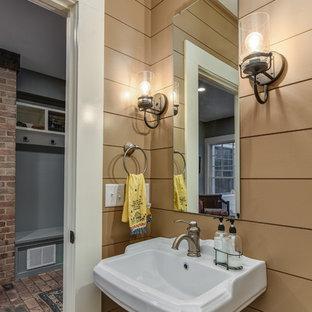 Неиссякаемый источник вдохновения для домашнего уюта: маленький туалет в стиле кантри с бежевыми стенами, кирпичным полом и раковиной с пьедесталом