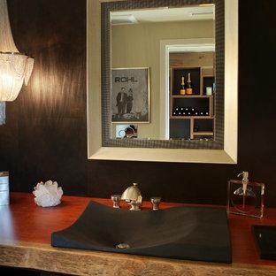 Идея дизайна: маленький туалет в стиле модернизм с черными фасадами, коричневыми стенами, настольной раковиной, столешницей из дерева, фасадами с декоративным кантом, коричневой плиткой и керамогранитной плиткой