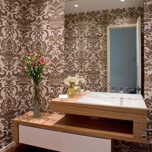 На фото: большой туалет в современном стиле с разноцветными стенами, полом из бамбука, монолитной раковиной и столешницей из дерева с