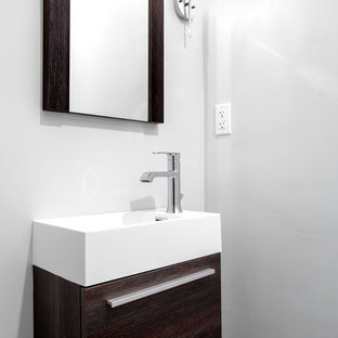 This is an example of a small cloakroom in Los Angeles with flat-panel cabinets, dark wood cabinets, a wall mounted toilet, multi-coloured tiles, porcelain tiles, grey walls, light hardwood flooring, an integrated sink, solid surface worktops, beige floors and white worktops.