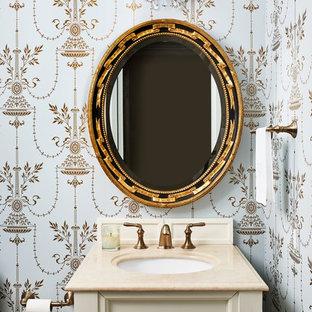 На фото: туалет в классическом стиле с фасадами с выступающей филенкой, бежевыми фасадами, разноцветными стенами, врезной раковиной и бежевой столешницей с