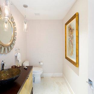 Пример оригинального дизайна: туалет среднего размера в современном стиле с фасадами с утопленной филенкой, желтыми фасадами, унитазом-моноблоком, бежевыми стенами, полом из керамогранита, настольной раковиной, столешницей из искусственного камня, бежевым полом и коричневой столешницей