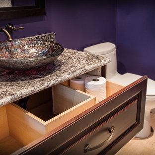 Kleine Klassische Gästetoilette mit verzierten Schränken, dunklen Holzschränken, Toilette mit Aufsatzspülkasten, lila Wandfarbe, hellem Holzboden, Aufsatzwaschbecken, Granit-Waschbecken/Waschtisch, beigem Boden und brauner Waschtischplatte in Edmonton