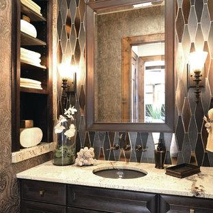Foto di un piccolo bagno di servizio design con lavabo sottopiano, ante con riquadro incassato, ante in legno bruno, piastrelle grigie, pareti multicolore e top bianco