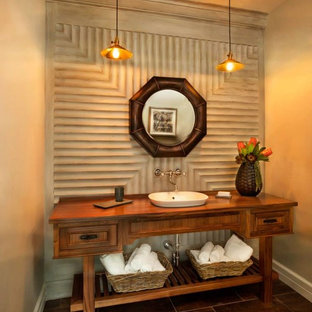 This is an example of a large tropical powder room in Portland with furniture-like cabinets, medium wood cabinets, beige walls, porcelain floors and wood benchtops.
