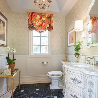 Powder room - traditional beige tile and black tile powder room idea in New York with an undermount sink, furniture-like cabinets, beige walls, distressed cabinets and white countertops