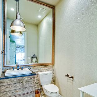 Идея дизайна: маленький туалет в стиле рустика с плоскими фасадами, светлыми деревянными фасадами, раздельным унитазом, бежевой плиткой, каменной плиткой, бежевыми стенами, полом из ламината, накладной раковиной, столешницей из гранита и бежевым полом