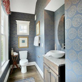 Exemple d'un WC et toilettes chic de taille moyenne avec un placard avec porte à panneau surélevé, des portes de placard en bois sombre, un WC séparé, un mur bleu, un sol en bois foncé, une vasque, un plan de toilette en granite et un sol marron.