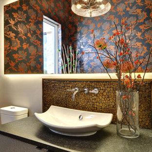 Immagine di un bagno di servizio minimal di medie dimensioni con lavabo a bacinella, ante lisce, ante grigie, top in granito, piastrelle marroni, piastrelle a mosaico e pareti grigie