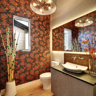 Mittelgroße Stilmix Gästetoilette mit Aufsatzwaschbecken, flächenbündigen Schrankfronten, grauen Schränken, Granit-Waschbecken/Waschtisch, Mosaikfliesen, bunten Wänden, braunem Holzboden und schwarzer Waschtischplatte in Austin