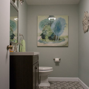 Cette image montre un petit WC et toilettes traditionnel avec un placard à porte plane, des portes de placard marrons, un WC à poser, un mur bleu, un sol en carrelage de céramique, un lavabo encastré, un plan de toilette en quartz et un sol multicolore.