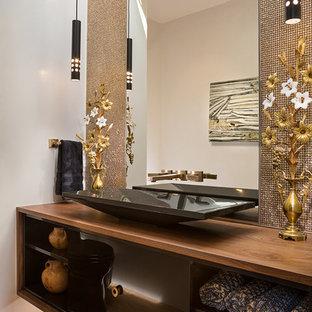 Foto på ett mellanstort funkis brun toalett, med öppna hyllor, svarta skåp, en toalettstol med hel cisternkåpa, brun kakel, kakel i metall, beige väggar, ljust trägolv, ett fristående handfat, träbänkskiva och beiget golv