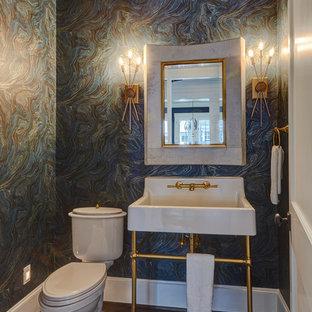 Modelo de aseo clásico, pequeño, con sanitario de dos piezas, paredes multicolor, suelo de madera oscura, lavabo tipo consola y suelo marrón
