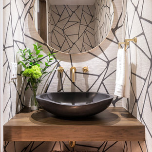 Inspiration for a contemporary dark wood floor and brown floor powder room remodel in Minneapolis with open cabinets, dark wood cabinets, multicolored walls, a vessel sink, wood countertops and brown countertops