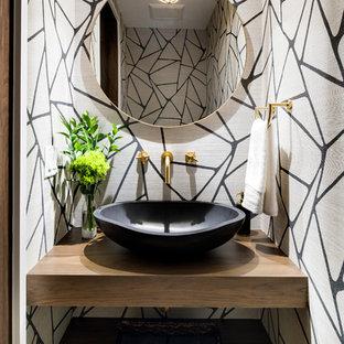 Imagen de aseo minimalista, pequeño, con armarios abiertos, puertas de armario de madera oscura, sanitario de una pieza, suelo de madera clara, lavabo sobreencimera, encimera de madera, suelo gris y encimeras marrones