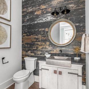 Idées déco pour un grand WC et toilettes campagne avec un placard avec porte à panneau encastré, des portes de placard blanches, un WC à poser, un carrelage blanc, des carreaux de céramique, un mur blanc, un sol en bois brun, un lavabo posé, un plan de toilette en granite, un sol multicolore et un plan de toilette noir.
