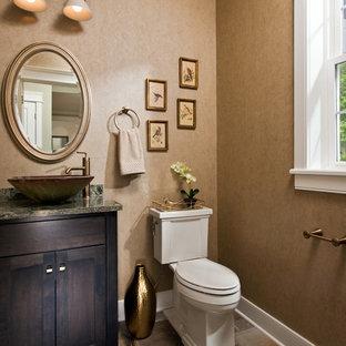 На фото: туалеты в классическом стиле с фасадами в стиле шейкер, темными деревянными фасадами, коричневыми стенами, настольной раковиной, коричневым полом и серой столешницей