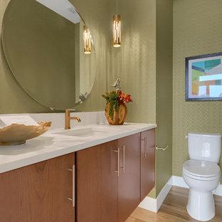 Свежая идея для дизайна: туалет среднего размера в современном стиле с плоскими фасадами, фасадами цвета дерева среднего тона, раздельным унитазом, зелеными стенами, светлым паркетным полом, врезной раковиной, столешницей из искусственного кварца, белой столешницей и бежевым полом - отличное фото интерьера