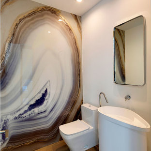 Medium sized contemporary cloakroom in Miami with a one-piece toilet, multi-coloured tiles, stone slabs, white walls, medium hardwood flooring, a pedestal sink, solid surface worktops, beige floors and white worktops.