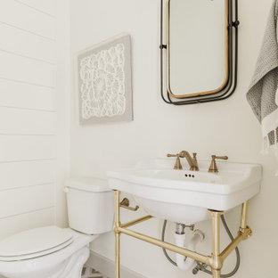 Klassisk inredning av ett badrum, med en toalettstol med separat cisternkåpa, vita väggar, cementgolv, ett konsol handfat och flerfärgat golv