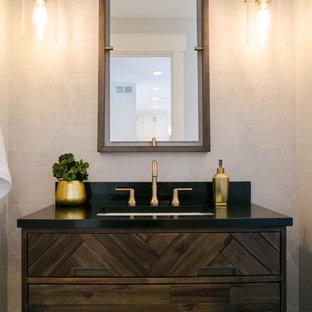 Mittelgroße Klassische Gästetoilette mit flächenbündigen Schrankfronten, dunklen Holzschränken, Toilette mit Aufsatzspülkasten, grauen Fliesen, Travertinfliesen, Unterbauwaschbecken, Quarzwerkstein-Waschtisch und schwarzer Waschtischplatte in Denver
