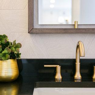 デンバーの中くらいのトランジショナルスタイルのおしゃれなトイレ・洗面所 (フラットパネル扉のキャビネット、濃色木目調キャビネット、一体型トイレ、グレーのタイル、トラバーチンタイル、アンダーカウンター洗面器、クオーツストーンの洗面台、黒い洗面カウンター) の写真