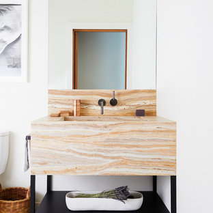Example of a trendy white floor powder room design in San Francisco with open cabinets, black cabinets, white walls, an undermount sink and beige countertops