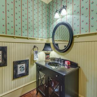 Idée de décoration pour un WC et toilettes champêtre avec un lavabo encastré, un mur multicolore, un sol en bois foncé, un placard à porte vitrée et des portes de placard en bois sombre.