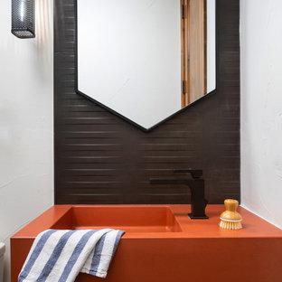 デンバーの小さいコンテンポラリースタイルのおしゃれなトイレ・洗面所 (オレンジのキャビネット、一体型トイレ、黒いタイル、セラミックタイル、白い壁、セラミックタイルの床、コンソール型シンク、コンクリートの洗面台、グレーの床、オレンジの洗面カウンター、フローティング洗面台) の写真