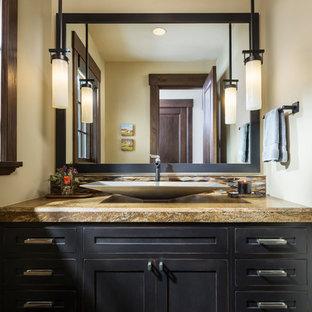 Foto de aseo rústico, pequeño, con armarios estilo shaker, puertas de armario negras, paredes beige, suelo de madera oscura, lavabo sobreencimera, encimera de granito, suelo marrón y encimeras marrones