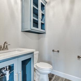 Пример оригинального дизайна: большой туалет в современном стиле с стеклянными фасадами, синими фасадами, унитазом-моноблоком, серыми стенами, светлым паркетным полом, врезной раковиной, столешницей из искусственного кварца и разноцветной столешницей