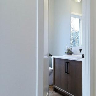Стильный дизайн: туалет среднего размера в современном стиле с плоскими фасадами, синими стенами, светлым паркетным полом, настольной раковиной, столешницей из искусственного кварца и темными деревянными фасадами - последний тренд