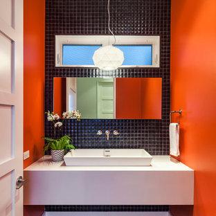 Foto de aseo actual con lavabo sobreencimera, baldosas y/o azulejos negros, sanitario de dos piezas, baldosas y/o azulejos en mosaico, parades naranjas y suelo de madera oscura