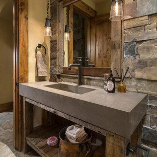 На фото: огромный туалет в стиле рустика с открытыми фасадами, фасадами цвета дерева среднего тона, коричневой плиткой, серой плиткой, каменной плиткой, желтыми стенами, монолитной раковиной, серым полом и серой столешницей