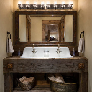 Idées déco pour un très grand WC et toilettes montagne avec un mur gris, un lavabo posé, un plan de toilette en bois, un sol gris et un plan de toilette marron.