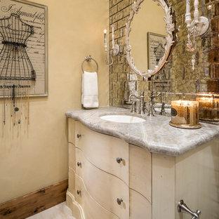 Idées déco pour un très grand WC et toilettes romantique avec un placard à porte plane, des portes de placard beiges, un carrelage gris, des carreaux de miroir, un mur beige, un lavabo encastré, un sol beige et un plan de toilette gris.