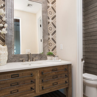 Photo of a mediterranean powder room in Phoenix with furniture-like cabinets, medium wood cabinets, a two-piece toilet, slate floors, an undermount sink, beige floor, beige walls and white benchtops.