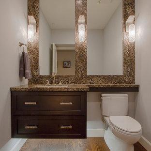 Idées déco pour un grand WC et toilettes contemporain avec un placard à porte shaker, des portes de placard marrons, un WC séparé, un mur gris, un sol en bois brun, un lavabo encastré, un plan de toilette en granite, un sol marron, un carrelage marron, des dalles de pierre et un plan de toilette marron.